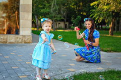 Mom and daughter blow bubbles Royalty Free Stock Photography