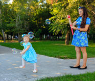 Mom and daughter blow bubbles Royalty Free Stock Photos