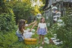 Mom and daughter blowing bubbles outdoors 4711. Mother with daughter blowing bubbles stock image
