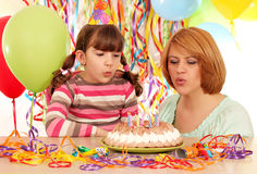 Mom and daughter blowing candles Royalty Free Stock Photography