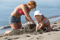 Mom and daughter are building a sand castle Royalty Free Stock Images