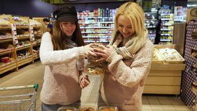 Mom and daughter buy cookies. In the supermarket, pastries in boxes stock footage