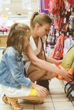 Mom and daughter buying school bag. stock images