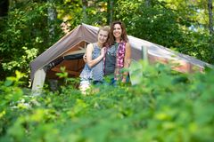 Happy mother and daughter camping in nature stock photography