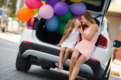 Mom and daughter in a car with balloons Stock Images