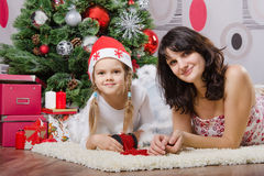 Mom and daughter are at the Christmas tree Royalty Free Stock Photos