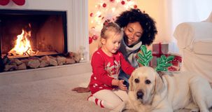 Mom and daughter in sweaters play with pet dog stock image