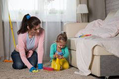 Mom and daughter are cleaning in the apartment Stock Photo