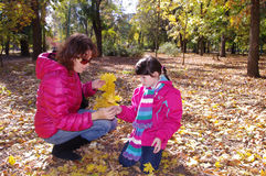 Mom and daughter collect autumn leaves. Mother and daughter walking in the autumn park stock photography