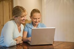 Mom and daughter with computer. Caucasian mid-adult woman and pre-teen  girl using laptop computer