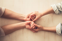 Mom and daughter. Cropped image of mom and daughter`s hands holding, on wooden background Royalty Free Stock Photos