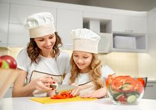 Mom and daughter cutting vegetables for fresh salad. stock images