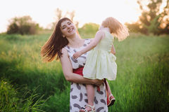 Mom and daughter dancing in nature together in sunset light Royalty Free Stock Photo