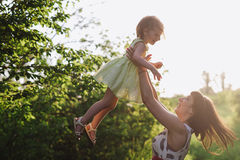 Mom and daughter dancing in nature together in sunset light Stock Images