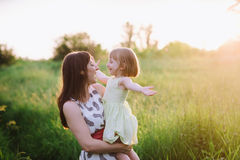 Mom and daughter dancing in nature together in sunset light Royalty Free Stock Image