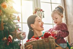 Mom and daughter decorate Christmas tree Stock Photo