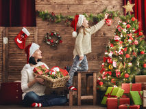 Mom and daughter decorate the Christmas tree. Stock Images