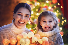 Mom and daughter decorate the Christmas tree. Stock Photography