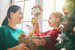 Mom and daughter decorate Christmas tree Royalty Free Stock Photos
