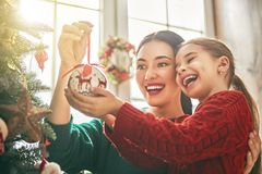 Mom and daughter decorate Christmas tree Royalty Free Stock Photo