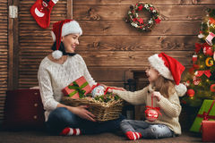 Mom and daughter decorate the Christmas tree. Royalty Free Stock Images
