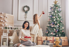 Mom and daughter decorate the Christmas tree. Stock Photos