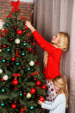 Mom with daughter decorate tree. Stock Photography