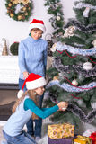 Mom and daughter decorating the Christmas tree Royalty Free Stock Images