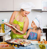 Mom and daughter decorating pizza Royalty Free Stock Image