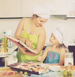 Mom and daughter decorating pizza Stock Photo