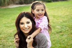 Mom and daughter. Diverse mom and daughter sitting in the grass stock photo