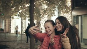Mom and daughter do selfie on a smartphone in the evening on a city street. Happy woman with a teenager taking pictures of herself with a phone camera stock video footage