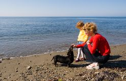 Mom.daughter.dog. Mom and the daughter play with a dog(dachshund) at the sea.Spring Royalty Free Stock Images