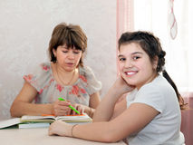 Mom and daughter doing homework at home. Stock Photography
