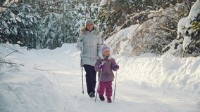 Mom and daughter doing nordic walking in the suburbs in winter. stock video