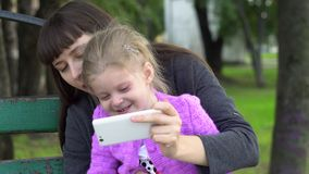 Mother and cute little daughter taking selfie with smartphone in the park. Mom with daughter are doing selfie or make a video call, the family shares their good stock footage