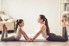 Mom and daughter doing yoga. Beautiful young women and her charming little daughter are smiling while doing yoga together at home Stock Image