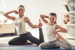 Mom and daughter doing yoga Stock Images
