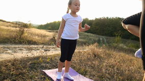 Mom and daughter doing yoga. Mom and daughter are engaged in yoga on the nature stock footage