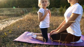 Mom and daughter doing yoga. Mom and daughter are engaged in yoga on the nature stock video footage