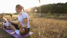 Mom and daughter doing yoga. Mom and daughter are engaged in yoga on the nature stock video