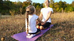 Mom and daughter doing yoga stock video footage