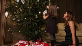 Mom and daughter dress up a Christmas tree on Christmas Eve.  stock video footage