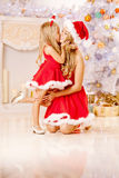 Mom and daughter dressed as Santa celebrate Christmas. Family at. Mother and daughter dressed as Santa celebrate Christmas. Family at the Christmas tree. Woman Royalty Free Stock Photography