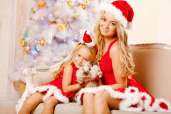 Mom and daughter dressed as Santa celebrate Christmas. Family at. Mother and daughter dressed as Santa celebrate Christmas. Family at the Christmas tree. Woman Royalty Free Stock Photo