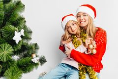 Mom and daughter are dressed in Santa Claus hats, in New Year`s stock photography