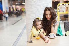 Mom and daughter drink coffee and juice in a cafe. Stock Photo