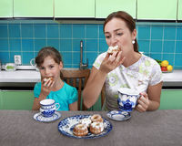 Mom and daughter eat muffins Stock Photos