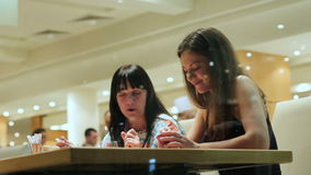 Mom and daughter eat in the restaurant and cute talk. View through a large window on two beautiful brunettes. Relations of native people stock video
