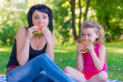 Mom and daughter eating tasty burgers Stock Photography